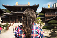 China, Hong Kong, Kowloon, back view of woman visiting Chi Lin nunnery - GEMF000095