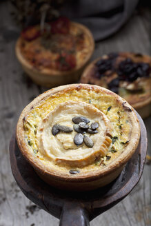 Courgette goat cheese tart with pumpkin seeds on wooden spoon - CSF024831