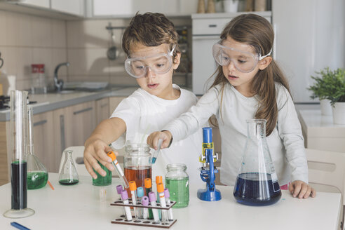 Boy and girl playing science experiments at home - DERF000023