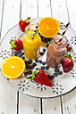 Orange and strawberry smoothie in glass bottles and fruits on plate - SARF001459
