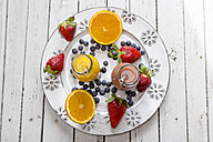 Orange and strawberry smoothie in glass bottles and fruits on plate - SARF001460