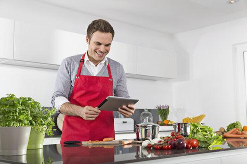 Smiling man using digital tablet while cooking - PDF000831