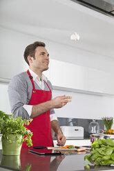 Smiling man juggling with garlic bulb in kitchen - PDF000834