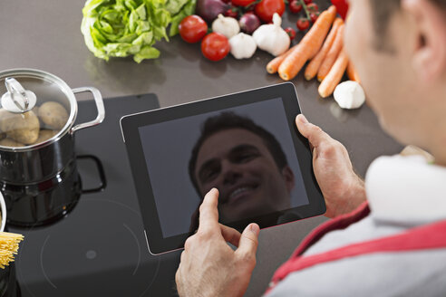 Display of digital tablet reflecting mirror image of smiling man in a kitchen - PDF000840