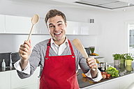 Portrait of smiling man with red apron and kitchen utensils - PDF000843
