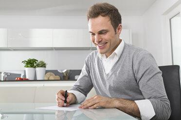 Smiling man sitting in kitchen writing down something - PDF000852