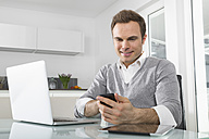 Smiling man sitting in kitchen with laptop using smartphone - PDF000855