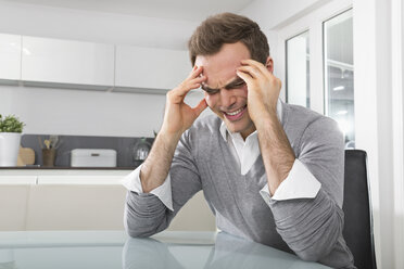 Man sitting in kitchen with hands on his face - PDF000858