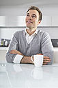Portrait of smiling man sitting in kitchen with cup of coffee - PDF000861