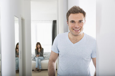 Portrait of smiling man standing in corridor while woman waiting in the background - PDF000867