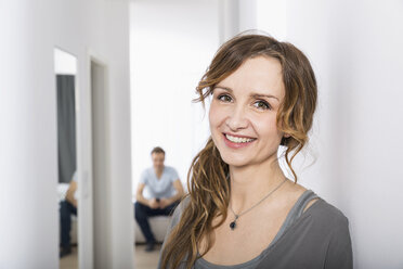 Portrait of smiling woman standing in corridor while man waiting in the background - PDF000870