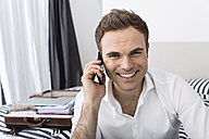 Smiling businessman sitting on bed telephoning with smartphone - PDF000892