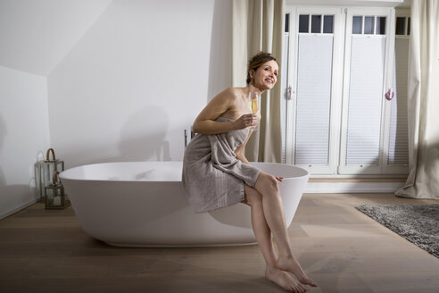 Woman sitting on the edge of modern bathtub with glass of champagne - PDF000881