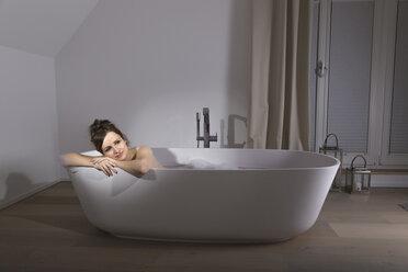 Smiling woman relaxing in modern bathtub - PDF000887
