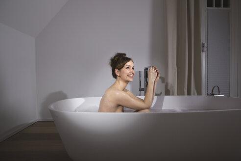 Smiling woman relaxing in modern bathtub - PDF000890