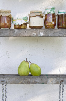 Row of preserving jars of pear chutneys and two fresh pears on wooden ladder - GIS000049