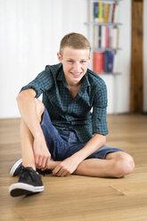 Smiling teenage boy sitting on floor - DRF001478