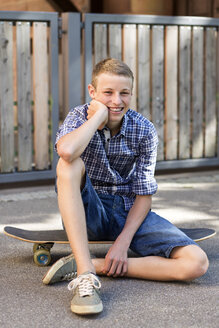 Smiling teenage boy sitting on skateboard - DRF001484