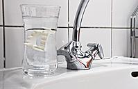 Vampire dentures in water glass on bathroom sink - STK001204