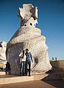Spain, Barcelona, couple kissing on rooftop of Casa Mila - GEM000109