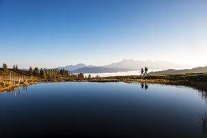 Austria, Altenmarkt-Zauchensee, hikers at mountain lake in the Lower Tauern - HHF005138