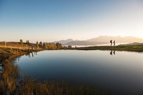 Austria, Altenmarkt-Zauchensee, hikers at mountain lake in the Lower Tauern - HHF005143