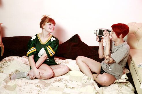 Woman filming her female friend with super 8 mm camera at home - VEF000050