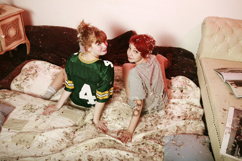 Two female friends on a blanket after pillow fight at home - VEF000055