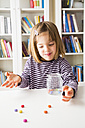 Little girl playing with chocolate buttons - LVF003036