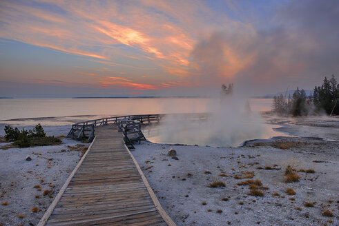 USA, Wyoming, Yellowstone National Park, sunrise at West Thumb Geyser Basin with wooden boardwalk - RUEF001533