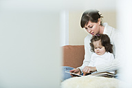 Woman and daughter looking at picture book - JTLF000050
