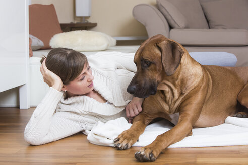 Woman caressing her Rhodesian Ridgeback dog - JTLF000053