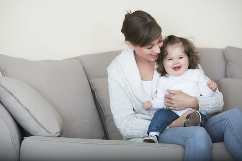 Woman with her daughter on couch - JTLF000058