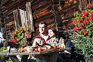 Austria, Altenmarkt-Zauchensee, couple having a break at alpine cabin - HHF005145