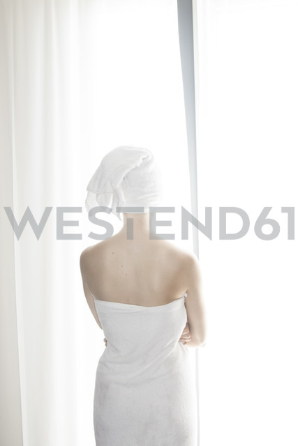 Woman wrapped in white towel standing in front of white curtain - CHPF000101 - Christophe Papke/Westend61