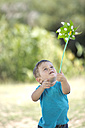 Little boy outdoors playing with paper windmill - ZEF003762