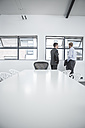 Two businessmen in the office at the window - ZEF004514