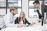Three businesspeople having an office meeting - ZEF004528