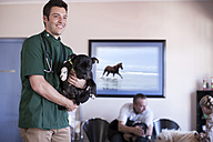Veterinarian holding a dog in the waiting room - ZEF005561