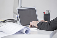 Close-up of businessman in office using laptop - ZEF004703
