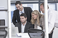 Smiling businesspeople in office looking at laptop - ZEF004656