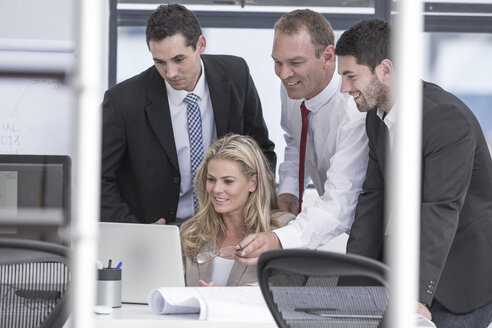 Smiling businesspeople in office looking at laptop - ZEF004657