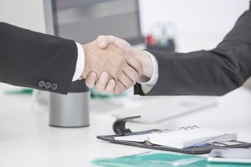 Close-up of two businessmen shaking hands in office - ZEF004662
