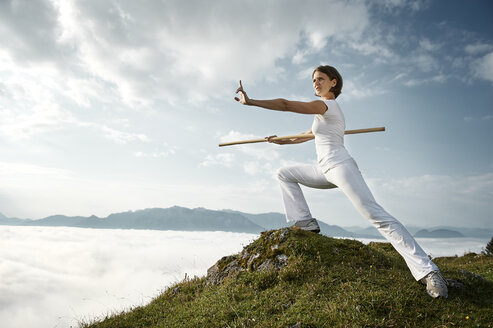 Austria, Kranzhorn, Mid adult woman exercising stick fighting on mountain top - MAOF000057
