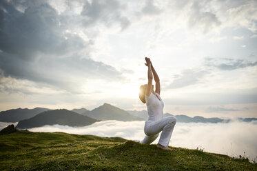 Austria.Kranzhorn, Mid adult woman practising yoga on mountain top - MAOF000018