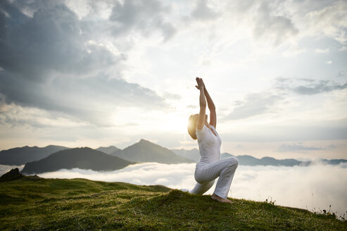 Austria.Kranzhorn, Mid adult woman practising yoga on mountain top - MAOF000018