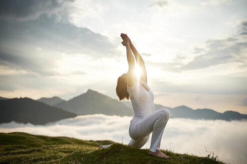 Austria.Kranzhorn, Mid adult woman practising yoga on mountain top - MAOF000019