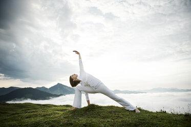 Austria.Kranzhorn, Mid adult woman practising yoga on mountain top - MAOF000027