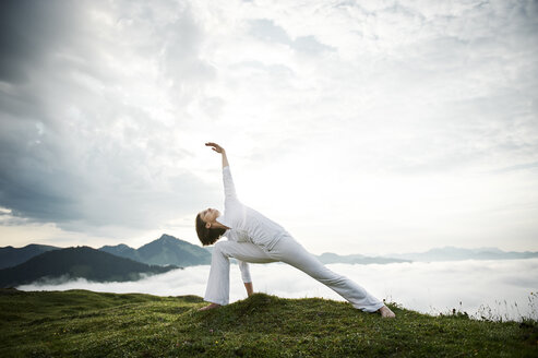 Austria.Kranzhorn, Mid adult woman practising yoga on mountain top - MAOF000027