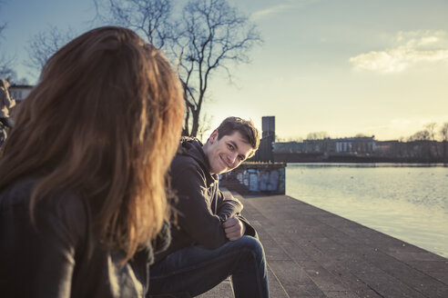 Germany, Berlin, teenage couple sitting face to face at lakeshore in the late afternoon - MMFF000531